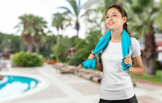 Woman after gym workout standing with towel