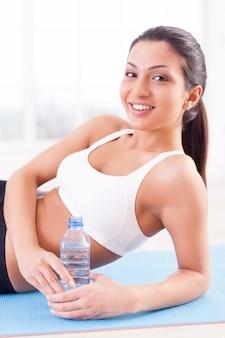 스포츠 훈련 후 여자입니다. 쾌활한 젊은 인도 여성 옆에 누워 물병을 들고