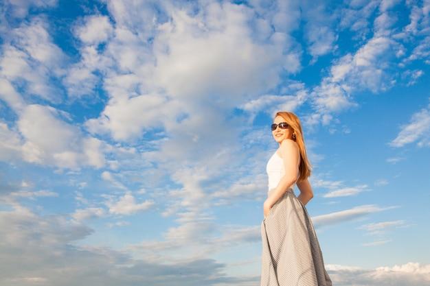 澄んだ青い空を背景の女性。