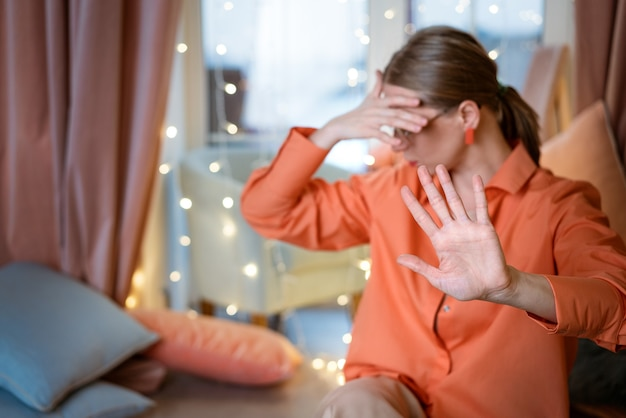 A woman against the background of a window in bright clothes covers her face with her hand and shows a stop gesture, soft focus. the concept of resentment and frustration