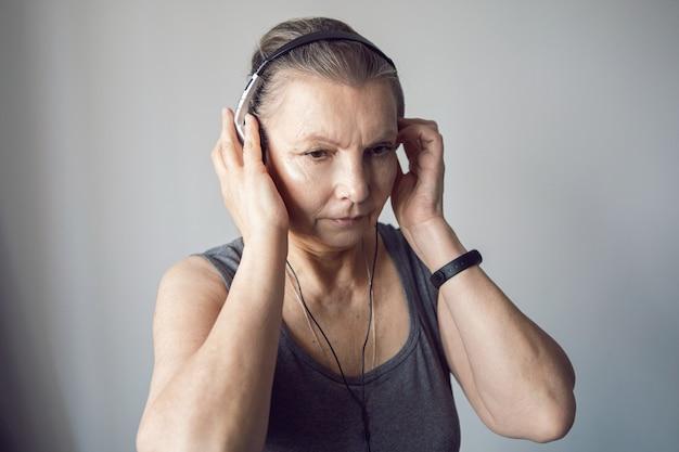 Женщина в возрасте спортсмен слушает музыку через наушники