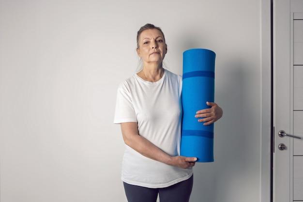 Женщина в возрасте спортсмен стоит в белой комнате с ковриком для йоги