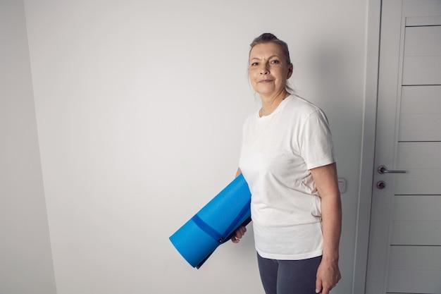 Спортсмен женщина в возрасте стоит в белой комнате с йогой
