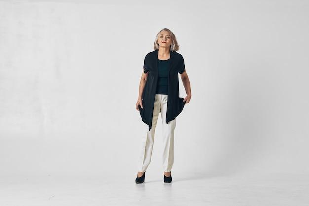 Женщина в возрасте модной одежды позирует в студии изолированного фона. фото высокого качества
