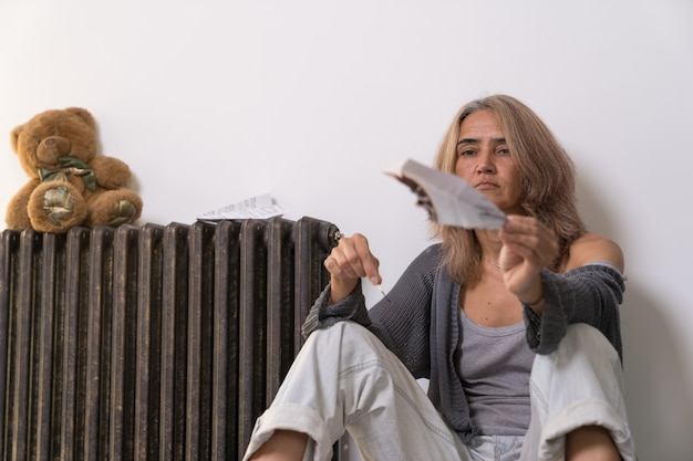 A woman aged sitting on the floor of an apartment burns a paper plane that she holds in her hand