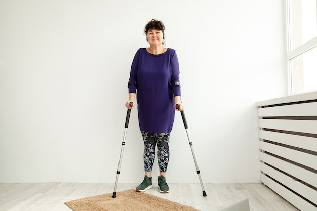 Woman aged stands on crutches in the office of physiotherapist. trauma recovery and rehabilitation concept.