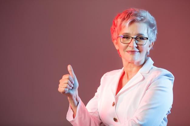 Женщина в возрасте, в очках, в белом пиджаке с жестом руки