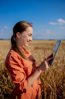Woman agronomist with tablet computer in the field of wheat checking quality and growth of crops for agriculture