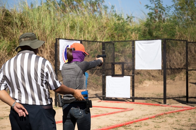 Woman aiming pistol in shooting range for competition