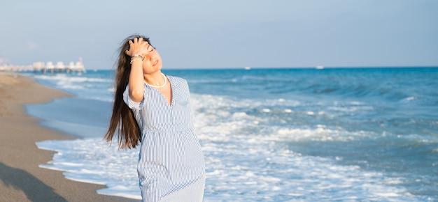 지중해에서 바람이 부는 날에 물결 모양의 바다와 수평선 너머로 보이는 바위 해변에서 혼자 여자. 고품질 사진