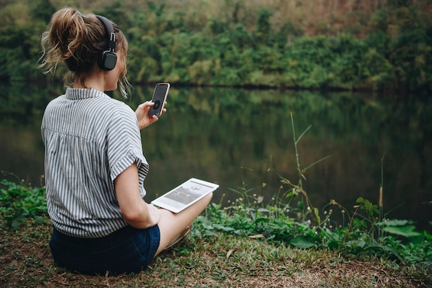 Woman alone in nature listening to music with headphones, digital tablet and a smartphone music and