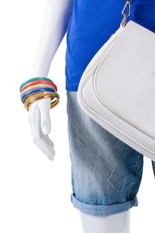 여성용 팔찌와 접힌 반바지. 마네킹에 접힌 데님 반바지. 팔찌가 달린 평범한 파란색 상의. 쇼케이스에 다채로운 플라스틱 액세서리입니다.