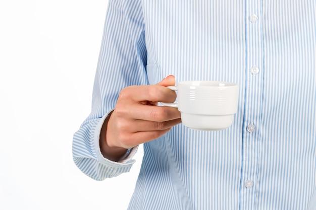 コーヒーカップを持っている女性の手。白いコーヒーカップを持つ実業家。素晴らしい朝のリフレッシュメント。休憩する時間です。