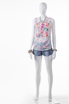 여성용 짧은 파란색 데님 반바지. 마네킹에 여름 데님 반바지입니다. 컬러풀한 상의와 데님 반바지. 아울렛 매장에서 여름 컬렉션입니다.