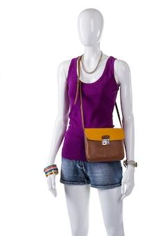 여성용 탑과 바이컬러 백. 흰색 마네킹에 바이 컬러 지갑입니다. 새 옷을 입은 다채로운 보석류. 옷에 잘 어울리는 색조합.
