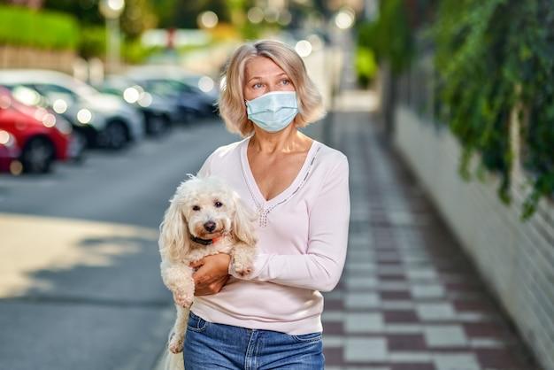 Женщина в антивирусной маске с собакой на руках на городской улице.
