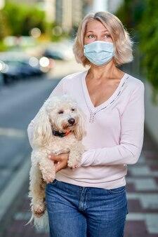 Женщина в антивирусной маске с собакой на городской улице.