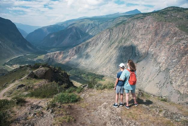 Женщина и ее сын на смотровой площадке долины реки чулышман. горы алтая, россия, прекрасный летний день, концепция путешествия