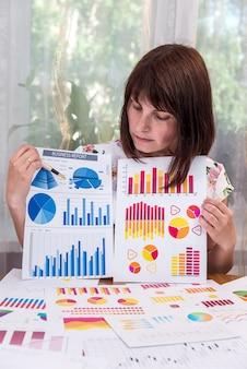 ビジネスグラフを表示し、それを指している女性アナリスト