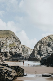 Женщина и собака стоят между двумя скалами на пляже