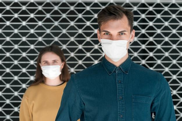 Женщина и мужчина в защитных масках стоят на расстоянии. концепция охраны здоровья