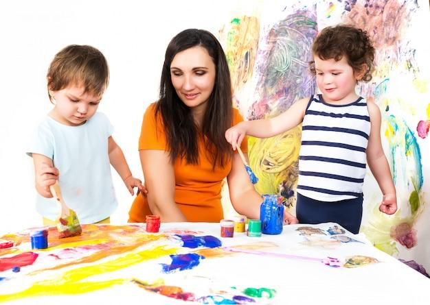 女性と赤ちゃんがテーブルに座りながら描く