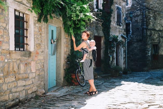 Groznjanクロアチアの歴史的な町の女性と赤ちゃん古いヨーロッパの通りに子供を持つ母