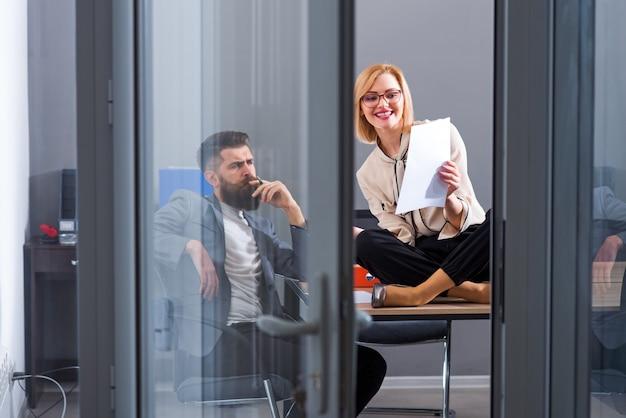 Женщина и бородатый мужчина работают вместе в офисе. женщина и хипстер пишут бизнес-план напряженного дня в офисе.