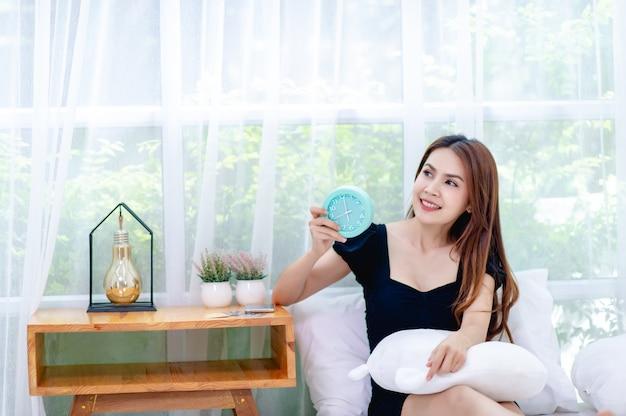 Женщина и постель по утрам просыпайтесь и радостно улыбайтесь концепция хорошего отдыха