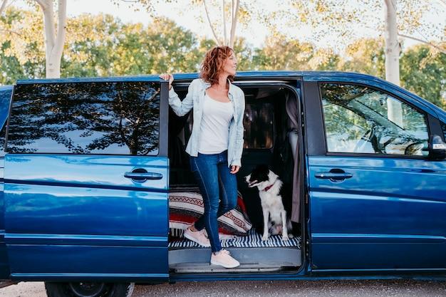 バンの女性とボーダーコリー犬。旅行のコンセプト