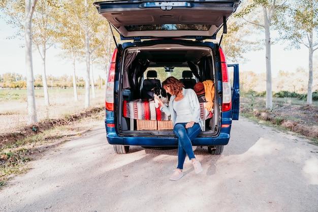 バンで女性とボーダーコリー犬。旅行のコンセプト