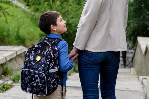 小学校の女性と少年の生徒は手をつないで行く