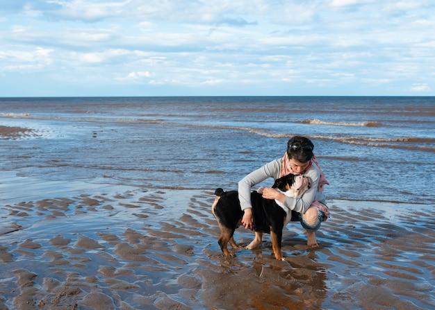 Женщина и британские английские бульдоги, сидя на берегу моря