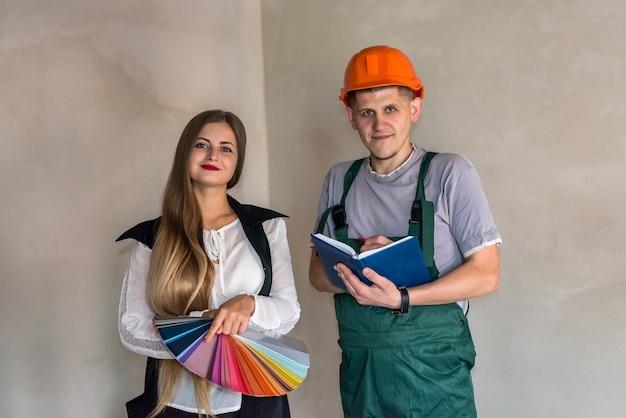 壁を塗るための色を選ぶ女性とビルダー