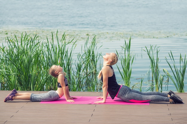 Женщина и ребенок тренируются возле озера на пирсе