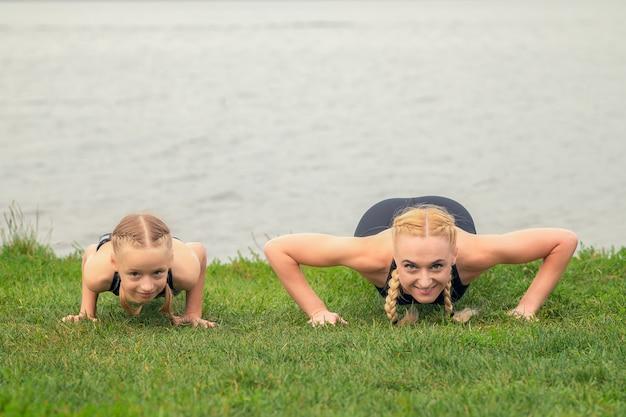 Женщина и ребенок тренируются у озера на зеленой траве