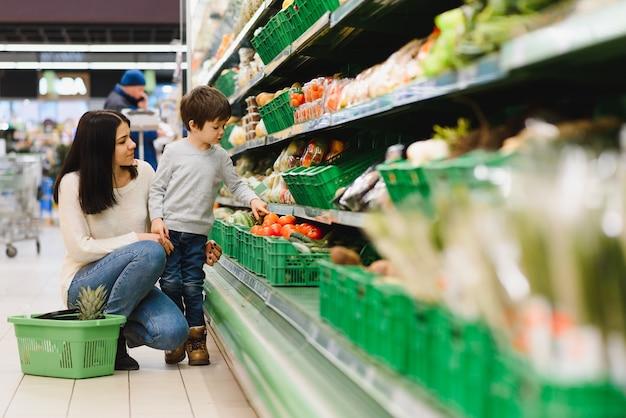 Женщина и ребенок мальчик во время семейных покупок с тележкой в супермаркете