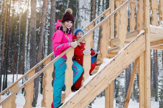 Женщина и ребенок поднимаются по деревянной горке. зимние русские забавы. яркая одежда, высокая деревянная гора, сосновый бор.