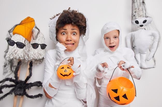 Женщина и ребенок испуганно смотрят в камеру, готовятся к вечеринке в честь хэллоуина, держат тыквы, наслаждаются тематическим мероприятием, устраивают счастливый семейный праздник. загадочный праздник и концепция декора