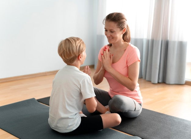 Женщина и ребенок на коврике для йоги полный снимок
