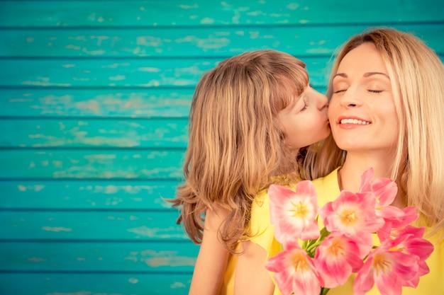 Женщина и ребенок с букетом цветов на зеленом фоне концепция семейного отдыха день матери