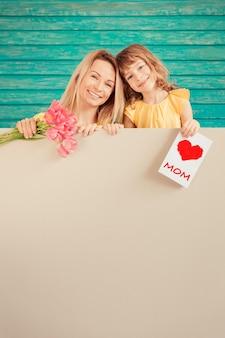 Женщина и ребенок с букетом цветов на зеленом фоне праздник концепции день матери