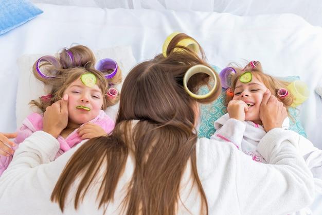 ベッドの上の女性と子供たち。