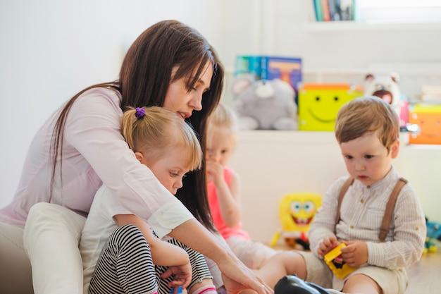 Женщина и дети, сидя на полу