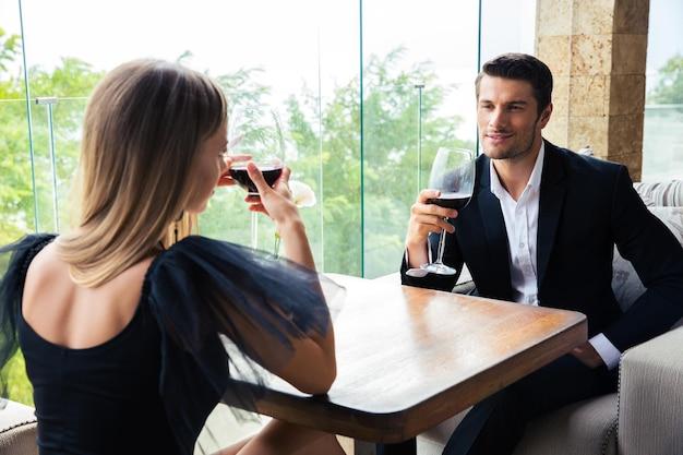 여자와 레스토랑에서 레드 와인을 마시는 자신감 남자