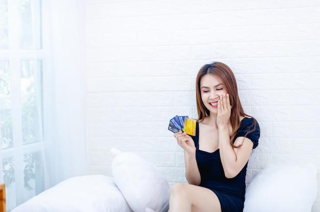 Деловая женщина с кредитной картой разговаривает по телефону и смотрит на кредитную карту бизнес-идея