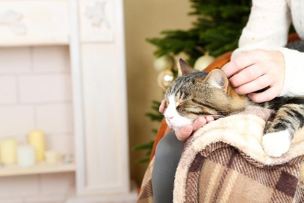 Женщина и милый кот сидят на кресле-качалке перед камином