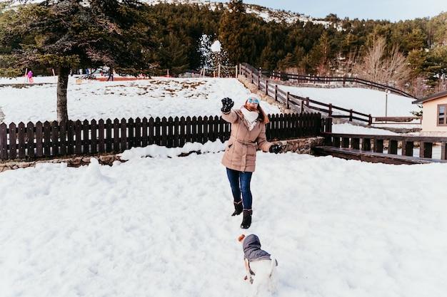 雪の山で野外を楽しんでいる女性とかわいいジャックラッセル犬。
