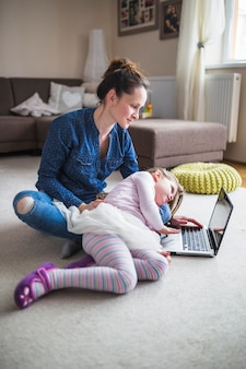 Woman and daughter looking at laptop screen