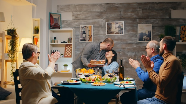 여자와 친구 및 가족과 함께 케이크를 들고 깜짝 식사를 하는 저녁 식사. 그녀는 촛불을 불고 있습니다. 슬로우 모션 촬영